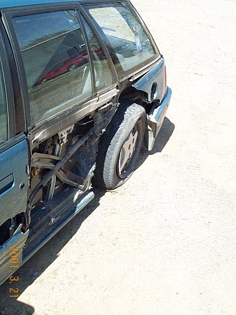 View of damage, standing at the front left of the car looking back towards.